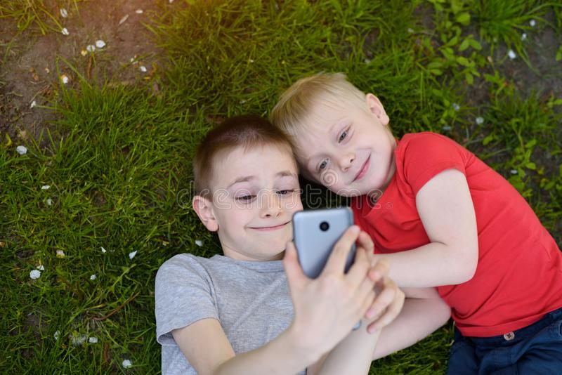 Två pojkar gör selfie på en smartphone, medan ligga på gräset Top besk?dar royaltyfri fotografi