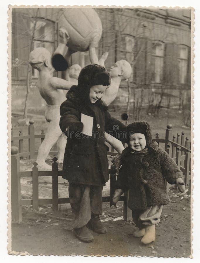 Två pojkar i vintern på en bakgrund av statyn royaltyfria foton