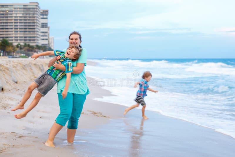Två pojkar och moder för små ungar på stranden av havet fotografering för bildbyråer