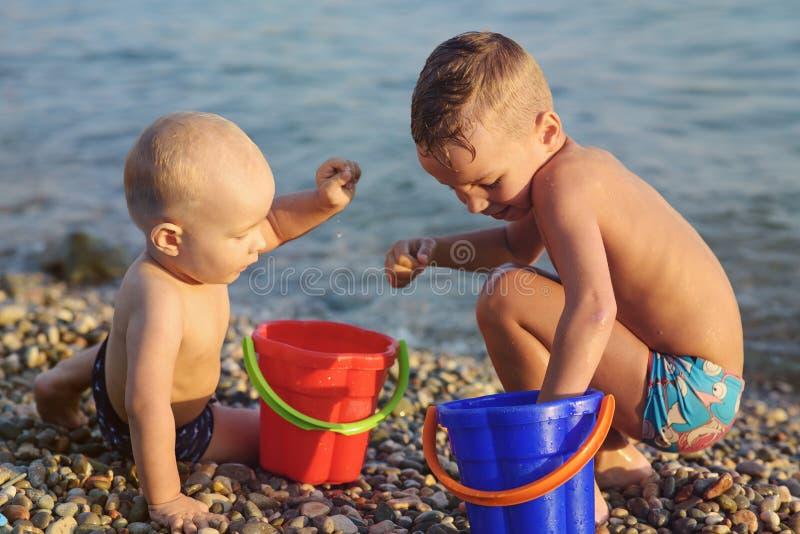 Två pojkar på Pebblet Beach arkivbilder