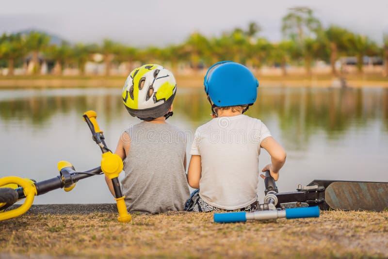 Två pojkar sitter på kusten av sjön, når de har ridit en cykel och en sparkcykel arkivfoto
