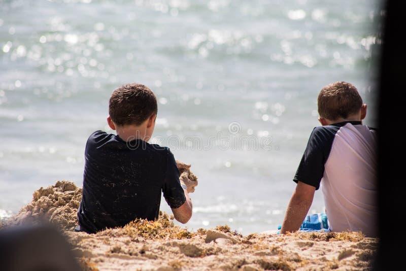 Två pojkar som är skämtsamma på semester på stranden med sand på en varm sommardag arkivfoton