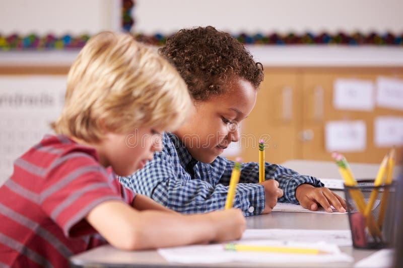 Två pojkar som arbetar på deras skrivbord i grundskolagrupp royaltyfri fotografi