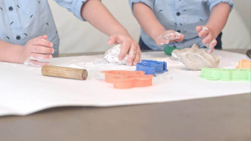 Två pojkar som förbereder deg för kakor samman med deras mum arkivbild
