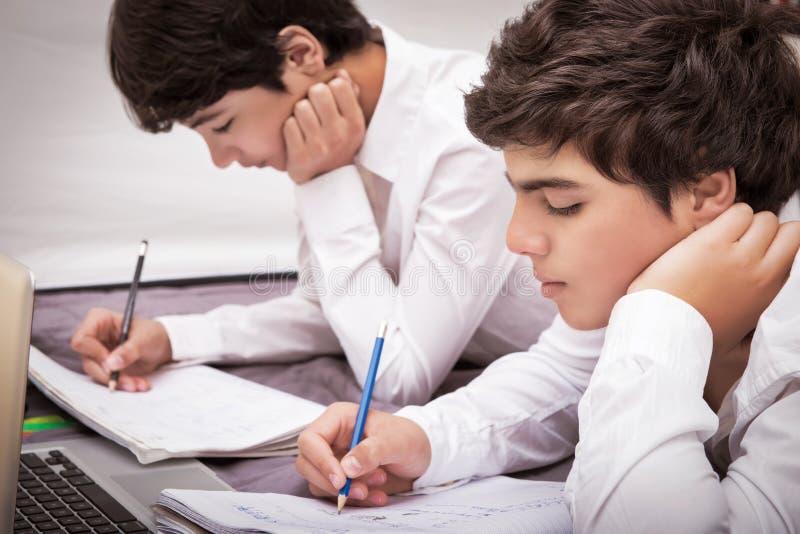 Två pojkar som gör läxa royaltyfri bild