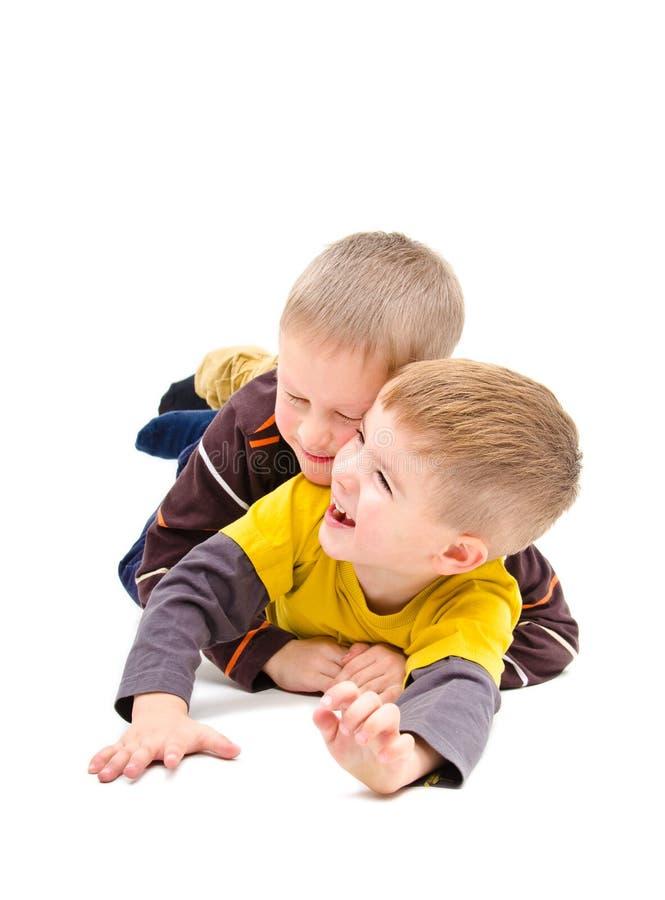 Två pojkar som har gyckel som skrattar att ligga royaltyfri foto