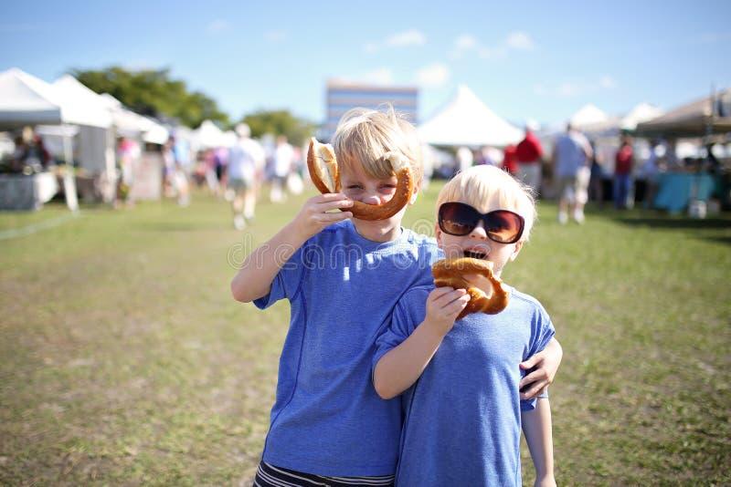 Två pojkar som har roligt äta Pretzles på marknaden för bonde` s arkivfoton