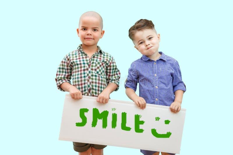 Två pojkar som rymmer ett tecken som säger leende royaltyfri bild