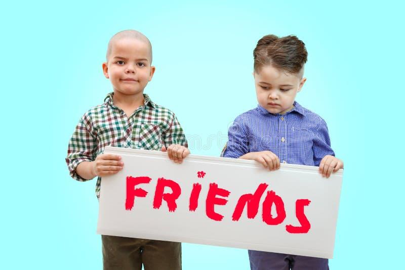 Två pojkar som rymmer ett tecken royaltyfri bild