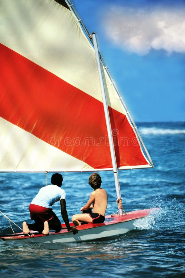 Två pojkar som seglar på den lilla segelbåten i det blåa havet royaltyfria bilder