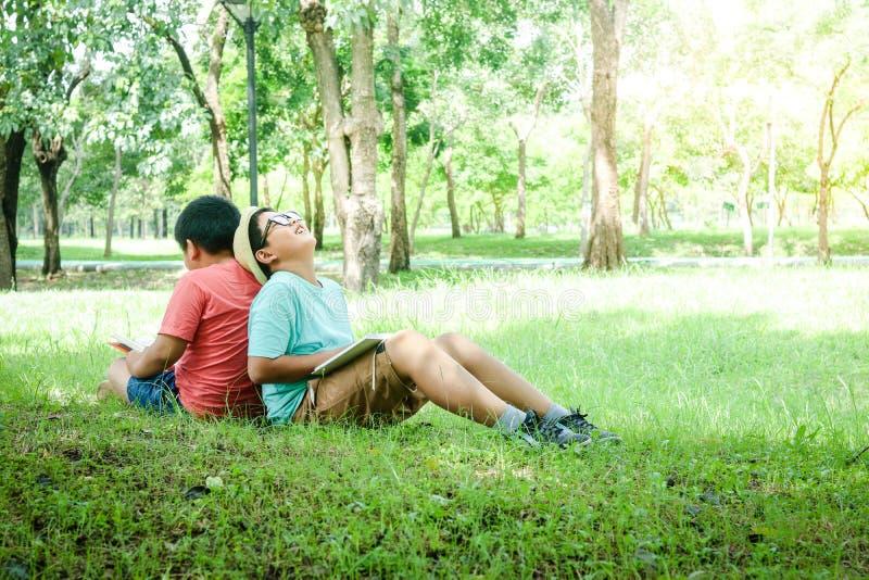 Två pojkar som sitter och läser i trädgården arkivfoton