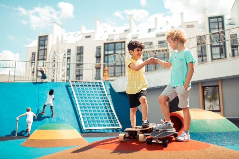 Två pojkar som skakar händer på en sportjordning royaltyfri bild