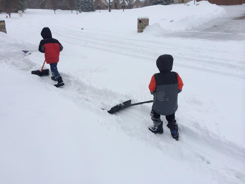 Två pojkar som skyfflar snö fotografering för bildbyråer