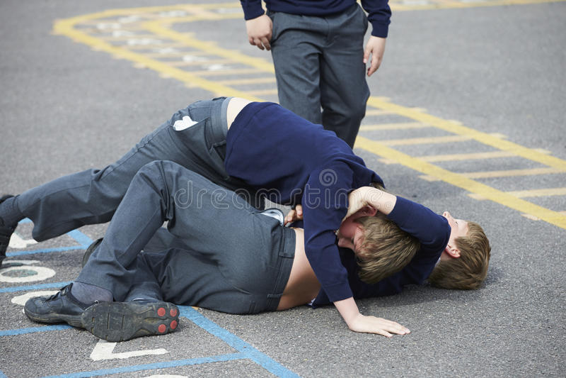 Två pojkar som slåss i skolalekplats royaltyfri foto
