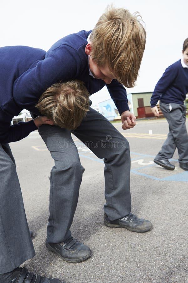 Två pojkar som slåss i skolalekplats fotografering för bildbyråer
