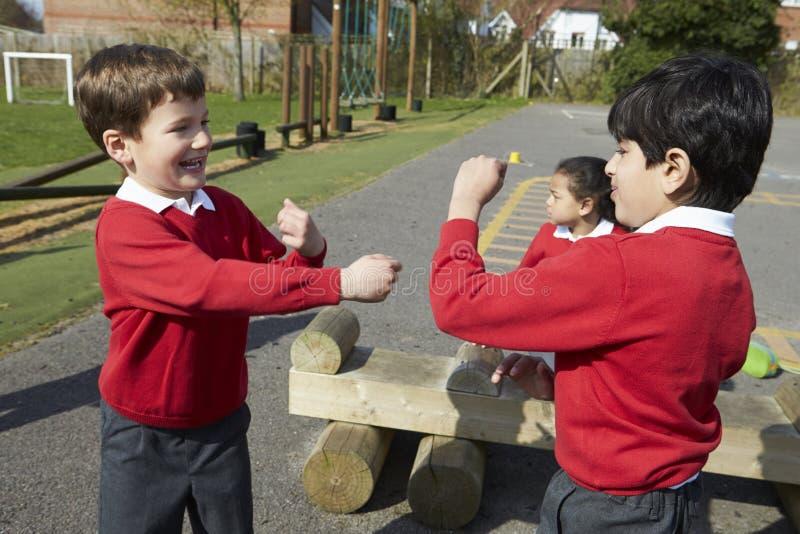 Två pojkar som slåss i skolalekplats royaltyfria foton
