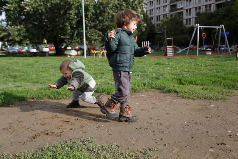 Två pojkar som spelar i lerig stadslekplats royaltyfri foto