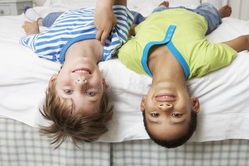 Två pojkar som spelar på säng tillsammans royaltyfri fotografi