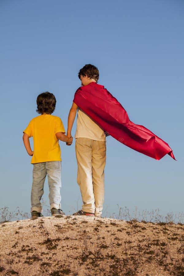 Två pojkar som spelar superheroes arkivfoton
