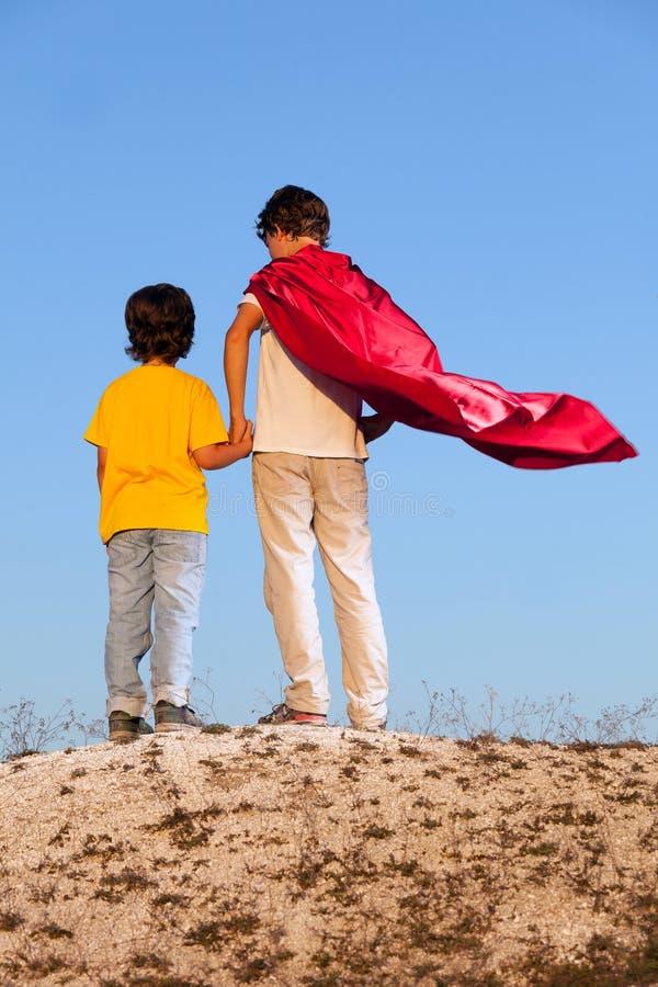 Två pojkar som spelar superheroes på himlen arkivfoto