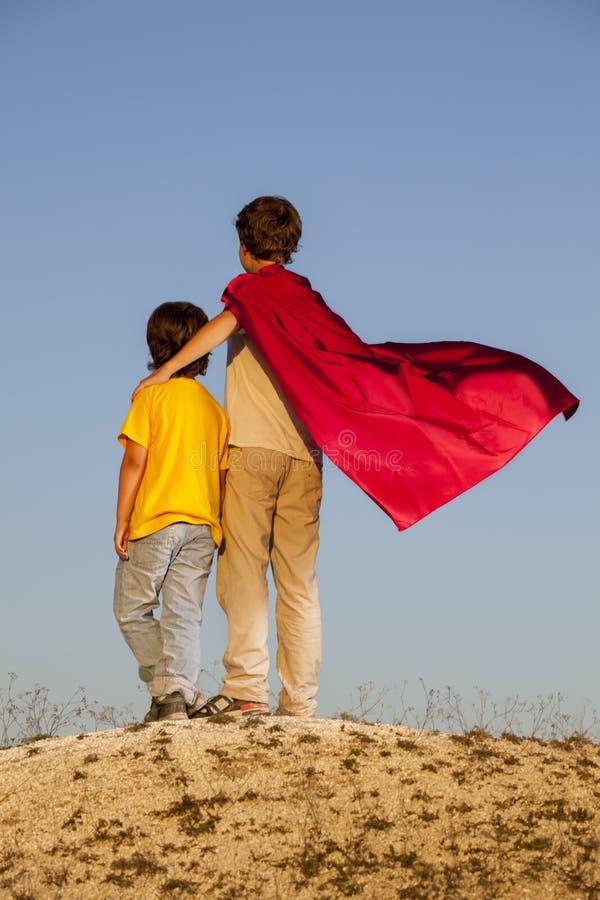 Två pojkar som spelar superheroes på himmelbakgrunden, Superheropr arkivbilder