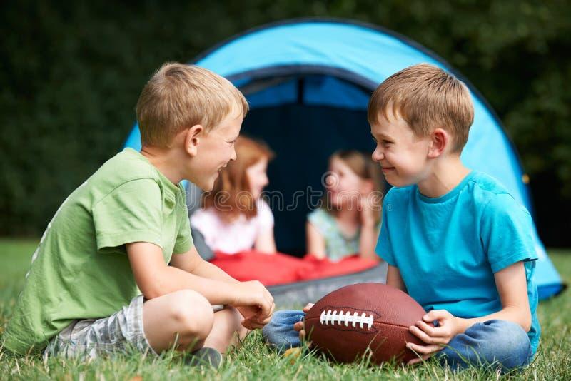 Två pojkar som talar och spelar med amerikansk fotboll på campa T arkivfoton