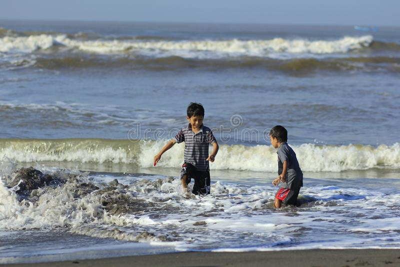 Två pojkar spelade vågor, tills deras kläder blöttes arkivbild
