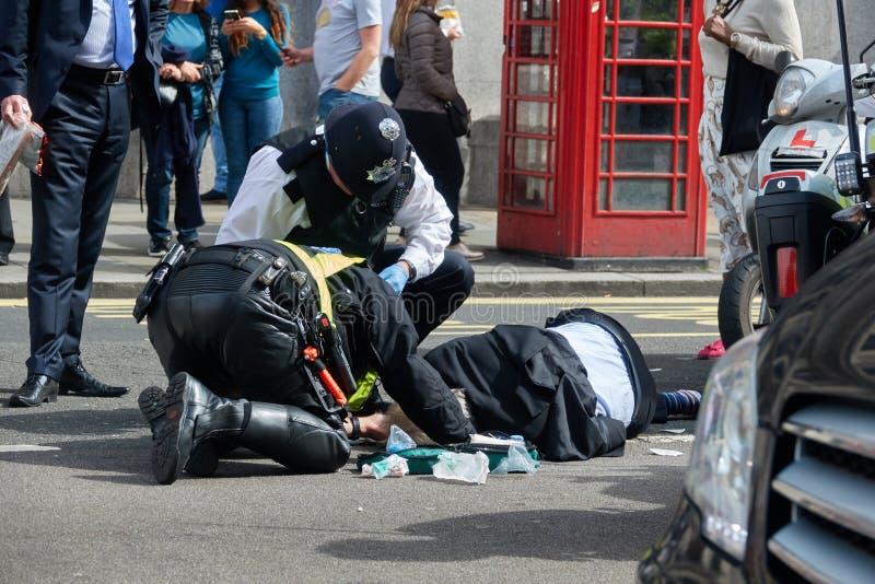 Två poliser hjälper en man som slås av en bil fotografering för bildbyråer