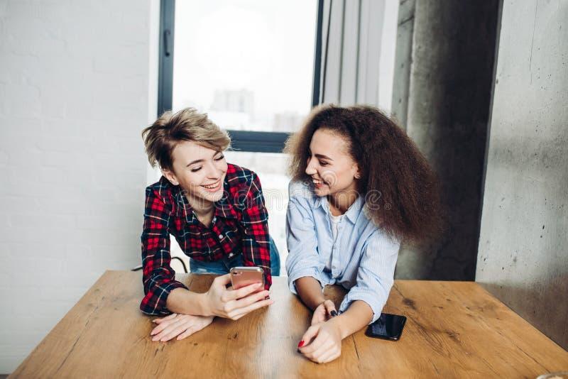 Två positiva flickor diskuterar meddelanden med de kamratskap royaltyfri bild