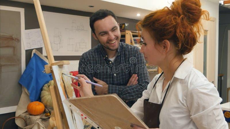 Två positiva konststudenter som skrattar i studion royaltyfri foto