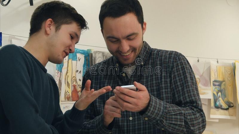 Två positiva konststudenter som skrattar på något på telefonen arkivbild