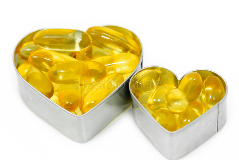 Två preventivpillerar för fiskolja på hjärta royaltyfri fotografi