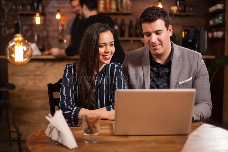 Två programmerare arbetar tillsammans på ett projekt i en coffee shop från deras bärbar dator fotografering för bildbyråer
