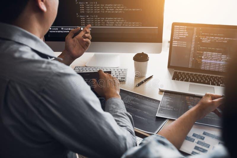 Två programvarubärare använder datorer för att arbeta samman med deras partner på kontorsskrivbordet arkivfoton