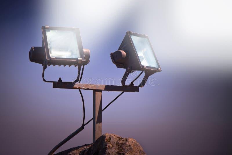 Två projektorer av ljus mot en himmelbakgrund - tonad bild arkivbild