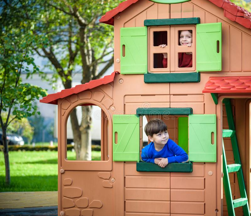 Två pyser som tillsammans spelar och har gyckel Livsstilfamiljögonblick av syskon på lekplats Ungevänner spelar på det hous träde fotografering för bildbyråer