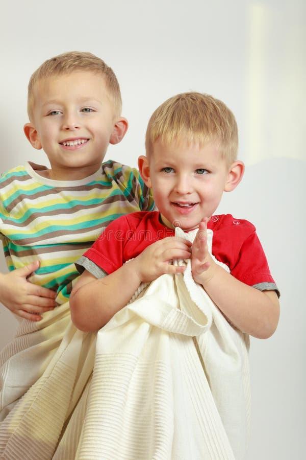 Två pyssyskon som spelar med handdukar royaltyfria bilder