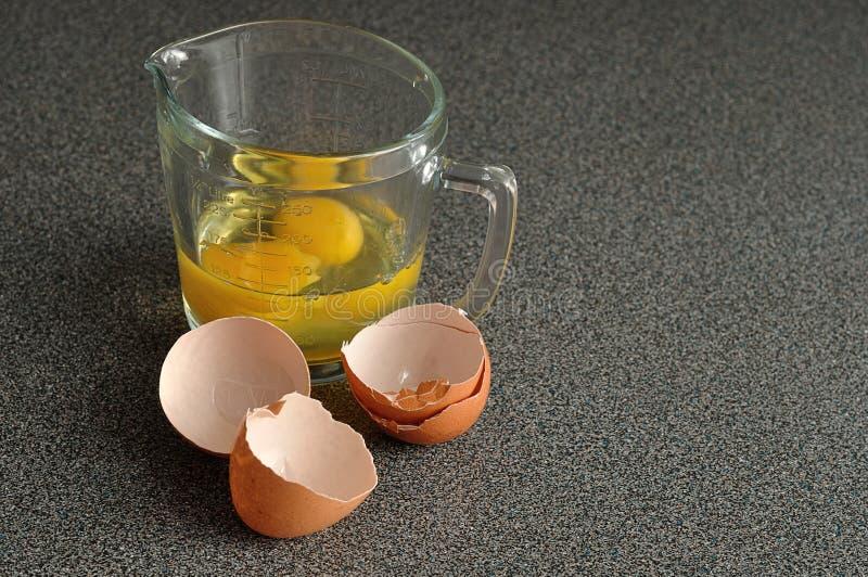 Två rå ägg i en mäta kopp med äggskal arkivfoton