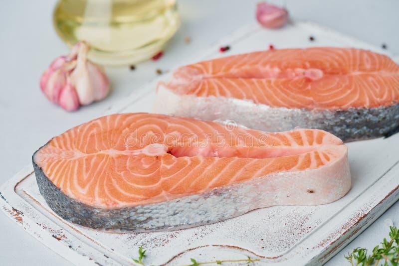 Två rå laxbiffar, fisk filea, stora skivade delar på en skärbräda på tabellen m?nga bakgrundsklimpmat meat mycket arkivbild
