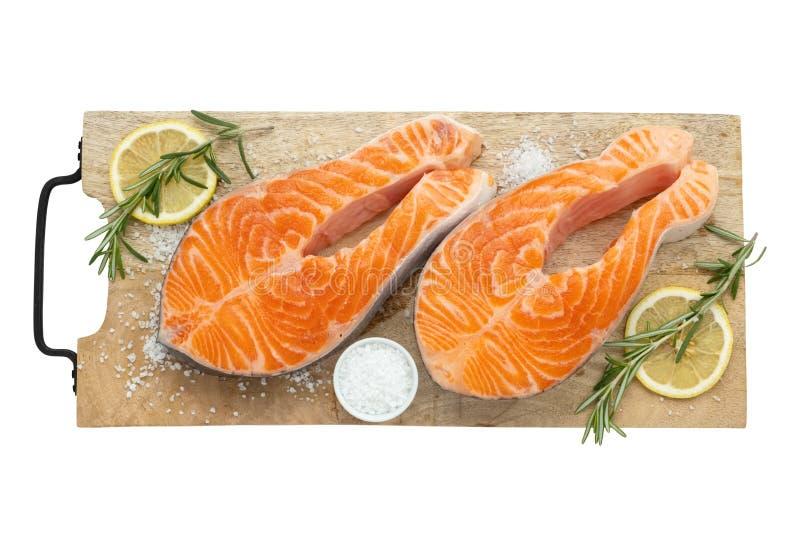 Två rå laxfiskbiffar med citronskivor, saltar och rosmarin på skärbräda royaltyfri fotografi