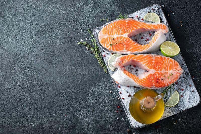 Två rå nya lax- eller forellbiffar som, är rika i olja omega-3, med limefrukt, timjan och olivolja på en mörk bakgrund Sunt och royaltyfri bild