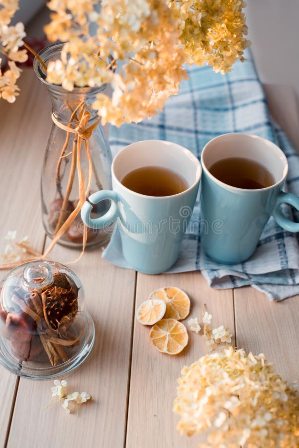 Två rånar av varmt te på en linneblåttservett Torkad vanlig hortensia, citron, kastanj, kanel royaltyfri bild