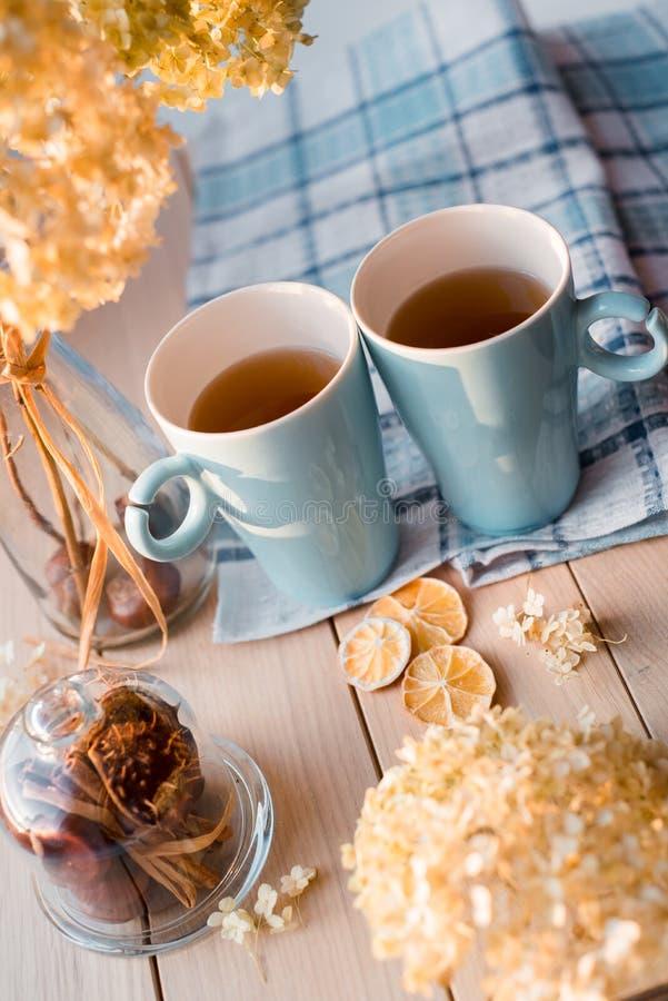 Två rånar av varmt te på en linneblåttservett Torkad vanlig hortensia, citron, kastanj, kanel royaltyfria foton