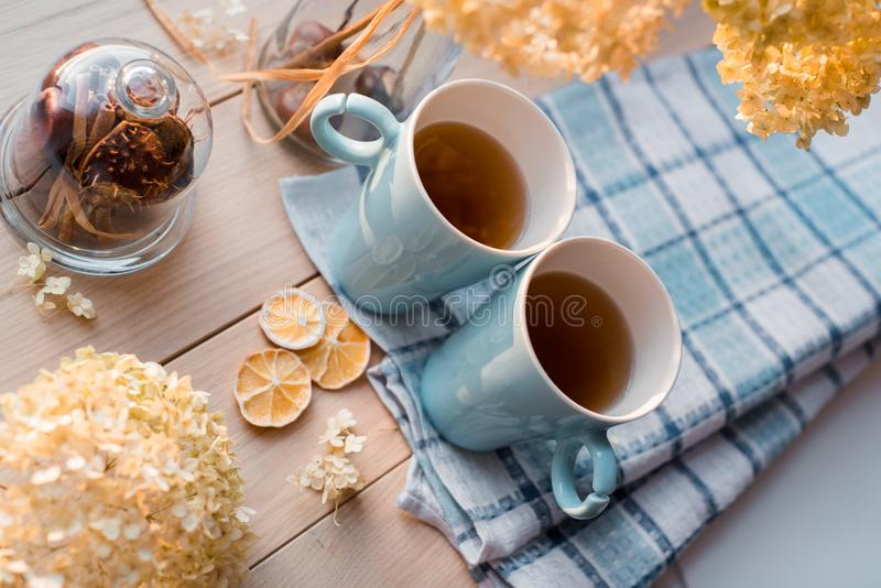 Två rånar av varmt te på en linneblåttservett Torkad vanlig hortensia, citron, kastanj, kanel arkivbild