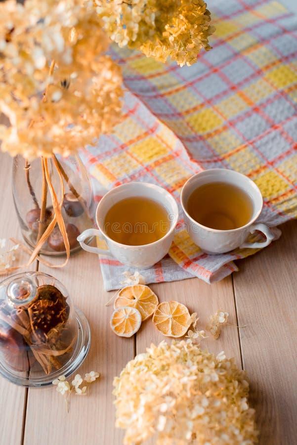Två rånar av varmt te på en linnegulingservett Torkad vanlig hortensia, citron, kastanj, kanel fotografering för bildbyråer