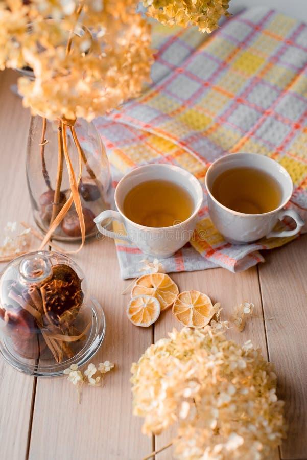 Två rånar av varmt te på en linnegulingservett Torkad vanlig hortensia, citron, kastanj, kanel royaltyfri bild