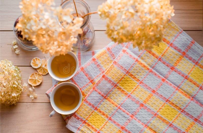 Två rånar av varmt te på en linnegulingservett Torkad vanlig hortensia, citron, kastanj, kanel Ställe för inskrift arkivbilder