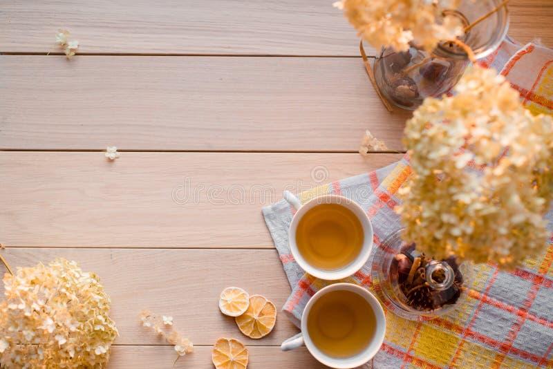 Två rånar av varmt te på en linnegulingservett Torkad vanlig hortensia, citron, kastanj, kanel Ställe för inskrift royaltyfria bilder