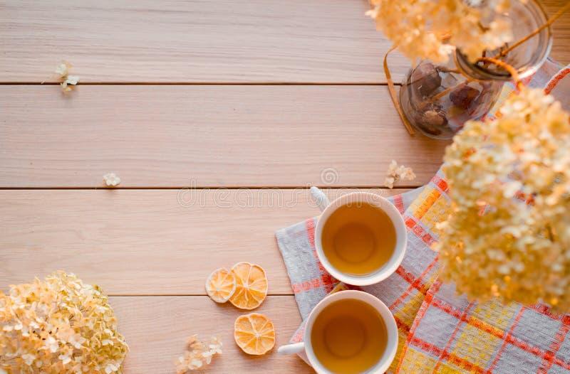 Två rånar av varmt te på en linnegulingservett Torkad vanlig hortensia, citron, kastanj, kanel Ställe för inskrift royaltyfri foto