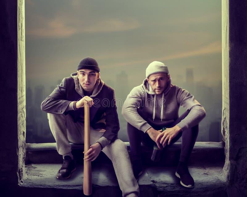 Två rånare squatting framme av fönstret royaltyfria foton